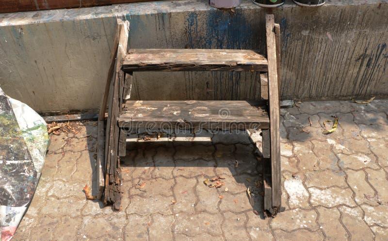 För växtkugge för tappning gammal trästol för stol för stege för hylla med smutsig väggbakgrund - utomhus- Garage/övergav Junkyar royaltyfri bild