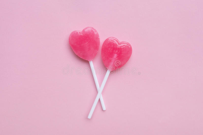 För valentin` s för två rosa färger godisen för klubban för form för hjärta för dagen på tomma pastellfärgade rosa färger skyler  royaltyfri bild