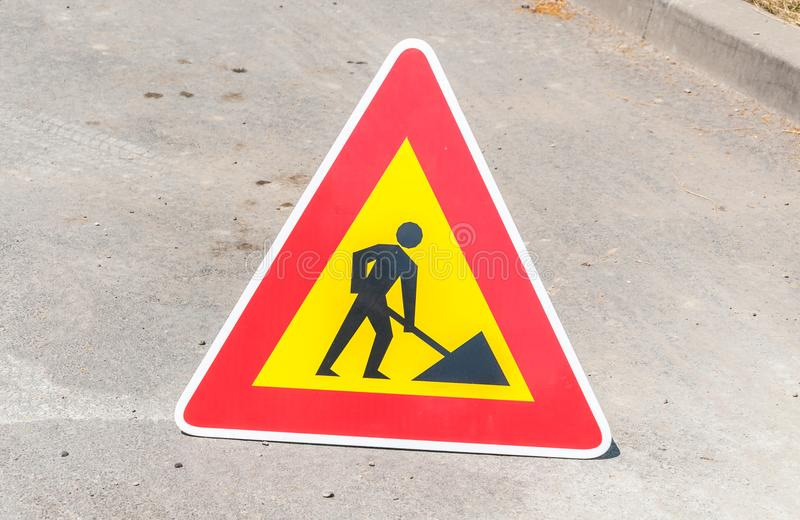 För varnings- eller varningstrafik för arbete vägmärke framåt på gatan arkivbild
