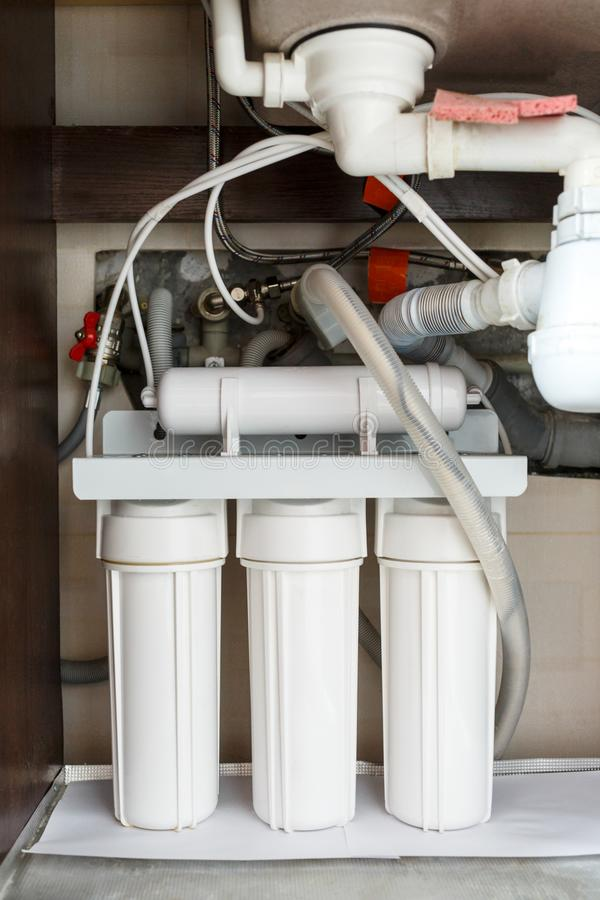För vattenrening för omvänd osmos system hemma Installation av filter för vattenrening under diskho i skåp arkivbild