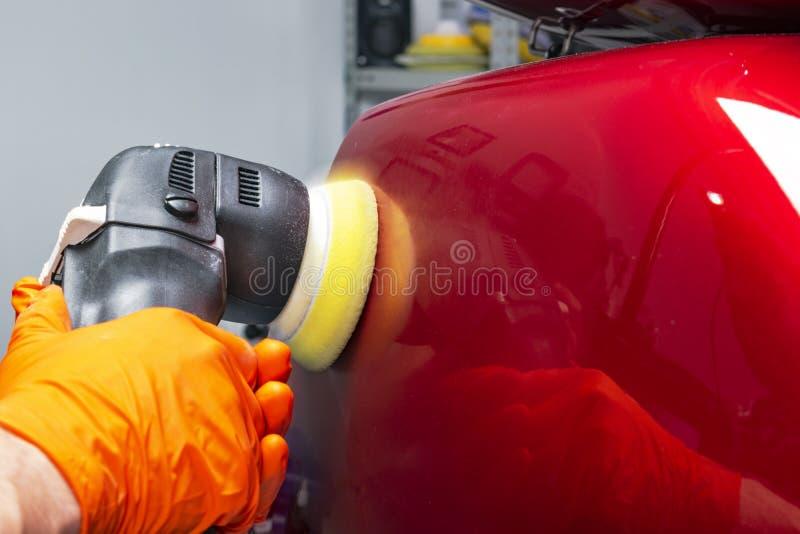 För vaxarbetare för bil som polska händer applicerar det skyddande bandet, innan polering Polerande och polerande bil Specificera fotografering för bildbyråer