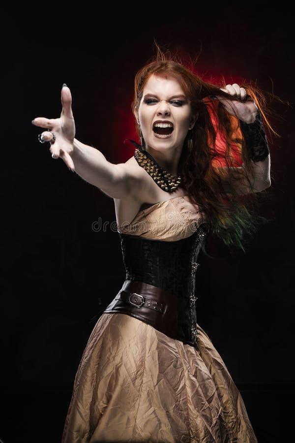 För Viktoriansk-stil för den härliga rödhårig mancosplayerflickan som bär klänningen steampunk skrin, drar hennes hår, vid hennes royaltyfri foto