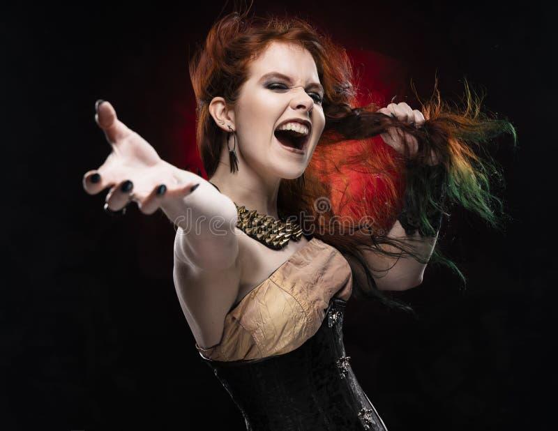 För Viktoriansk-stil för den härliga rödhårig mancosplayerflickan som bär klänningen steampunk skrin, drar hennes hår, vid hennes royaltyfria bilder