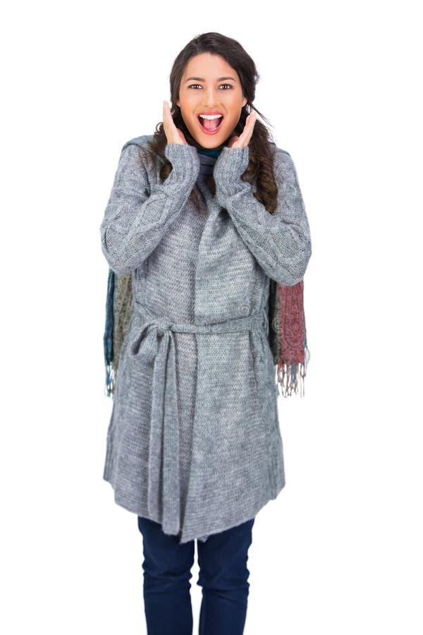 För vinterkläder för förvånad brunett bärande posera