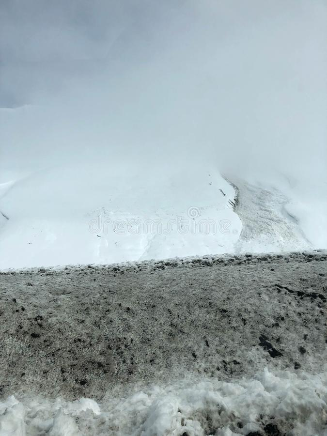 För vintersemesterort för härligt berg täckte kalla landskap med mist och snö för maxima för högt berg vaggar för snowboarding oc royaltyfria foton