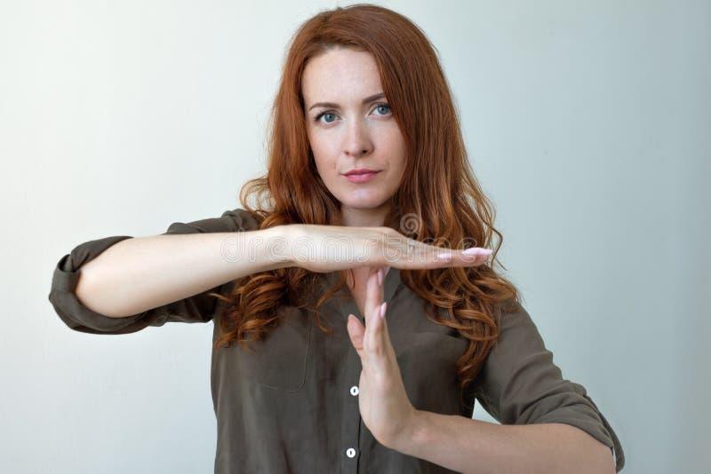För visningtid för den unga kvinnan gesten för handen ut, frustrerat skrika som ska stoppas, isolerade på grå väggbakgrund royaltyfria bilder
