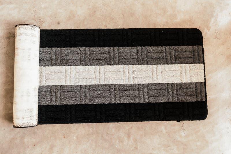 För vit för yoga matt svart randig design och grå färg på golvbakgrund Utrustning för yogagrupp Kondition och v?rd- ?vning royaltyfri bild