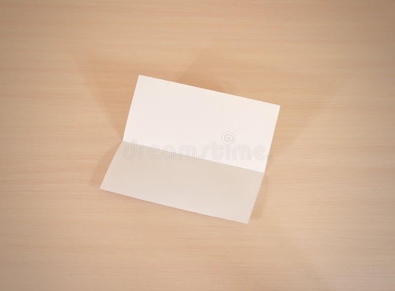 För vitbokbroschyr för broschyr tom modell på en trätabell Sho royaltyfri bild