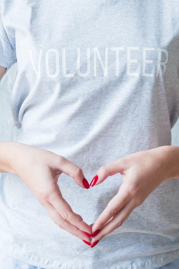 För volontärt-skjorta för kvinna grå medvetenhet för hjärta händer royaltyfri fotografi