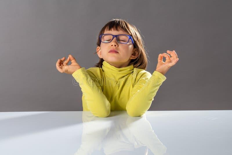 För yogabarn för Zen liten andning, praktiserande yoga och stängande ögon arkivbilder