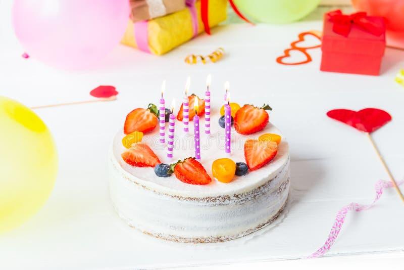 För yougurtbär för födelsedag sund kaka med stearinljus på färgrik partibakgrund med ljusa partihjälpmedel, garnering, gefts och  arkivbild
