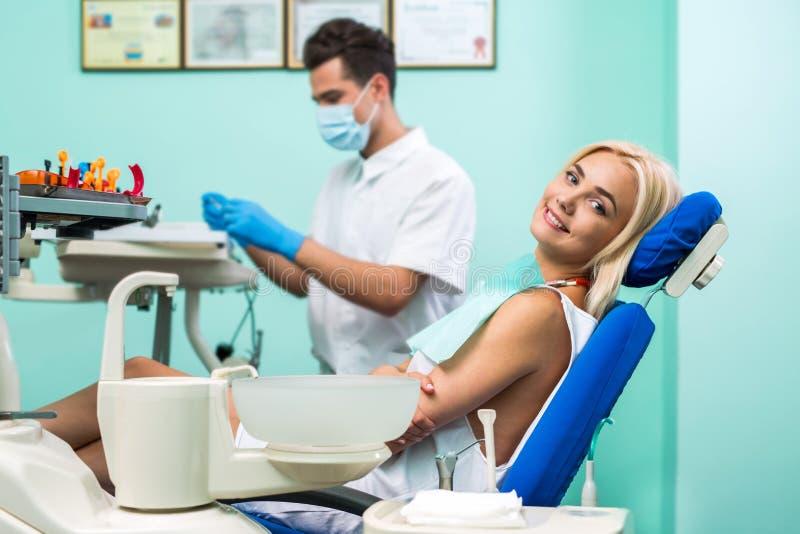 För Young för manlig tandläkare sammanträde blont flicka på tandläkaren och lookiing av kameran royaltyfria bilder