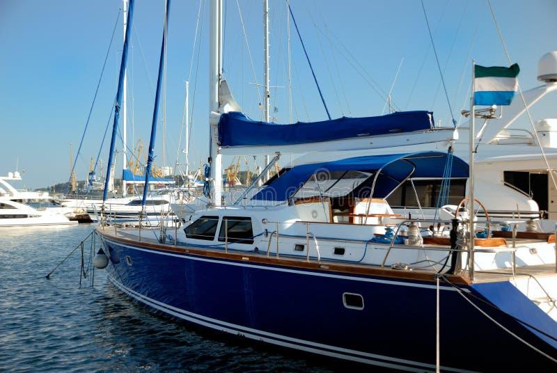 förankrad den blåa mörka seglingyachten royaltyfri bild