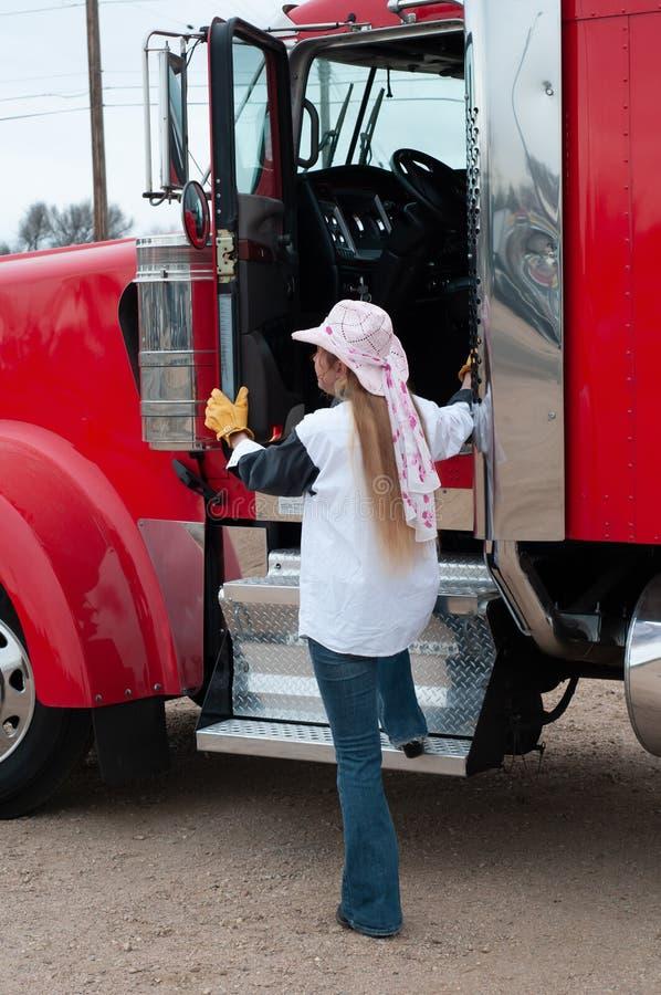 Förare av kvinnlig dragbil som kommer in i sin stora lastbil arkivfoto