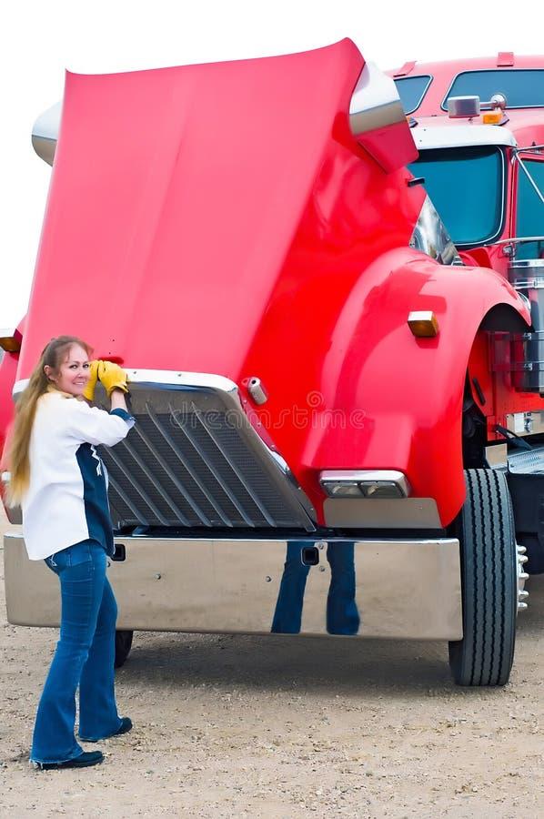Förare av kvinnliga lastbilar som drar i huven för att kontrollera motorvätskor royaltyfri fotografi