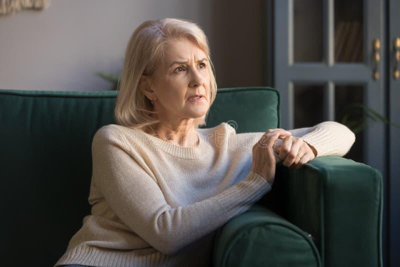 Förargad fundersam grå haired mogen kvinnakänsla som oroas om problem arkivfoto