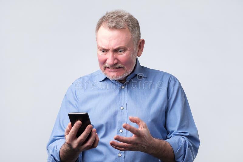 Förargad hög man i den blåa skjortan som ser mobiltelefonen fotografering för bildbyråer