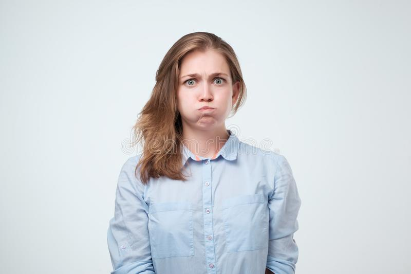 Förargad irriterad ung kvinnlig i blå skjorta som blåser henne kinder, rynka pannan som känner sig frustrerat med något royaltyfri bild
