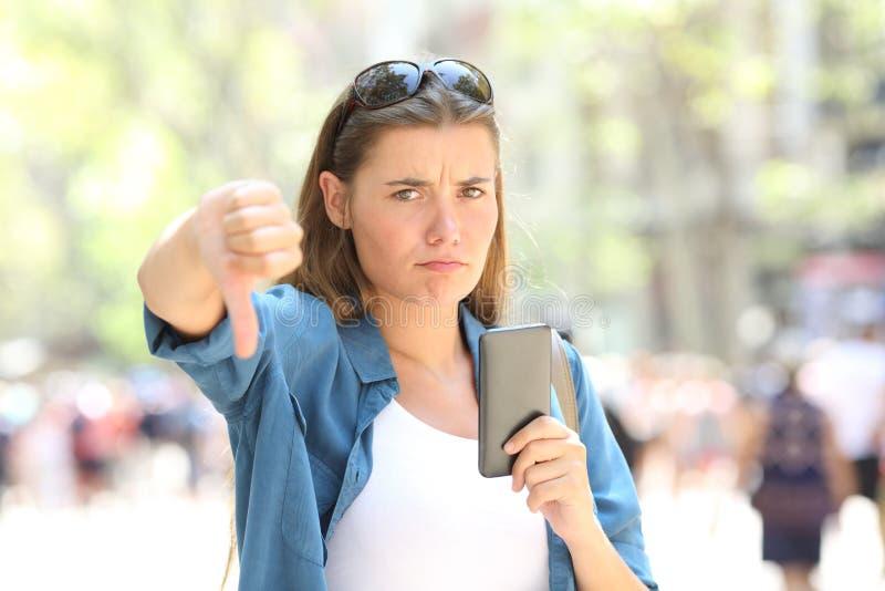 Förargad kvinna som rymmer en smart telefon med tummar ner royaltyfri foto
