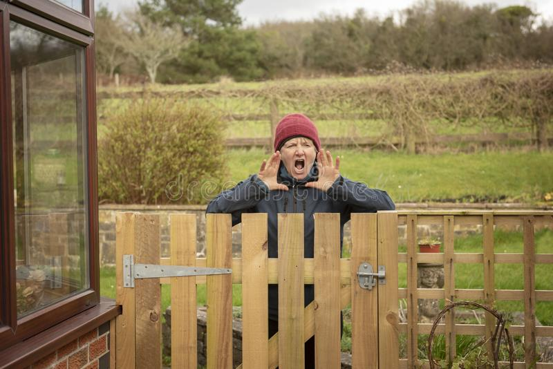 Förargad mogen kvinna som ropar över staketet fotografering för bildbyråer