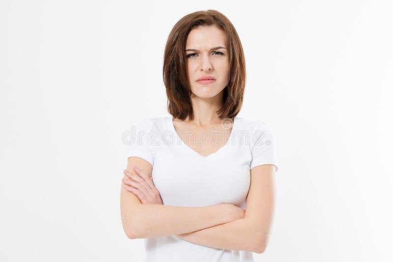 Förargad och ilsken flicka i den vita tomma t-skjortan som isoleras på vit bakgrund Ledsen och tokig kvinna med korsade armar kop arkivfoton