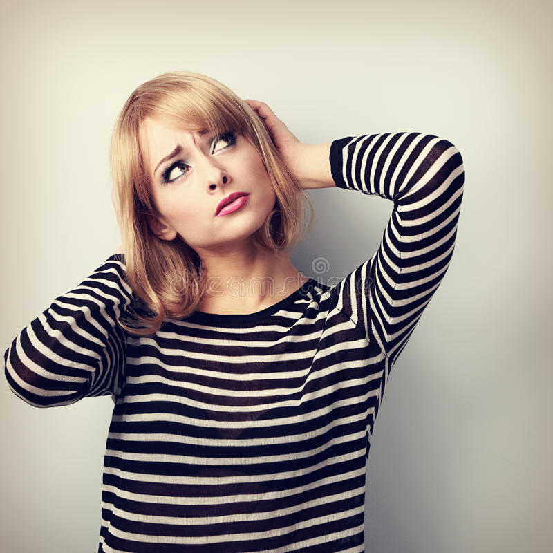Förargad olycklig tänkande ung kvinna som ser upp arkivfoto