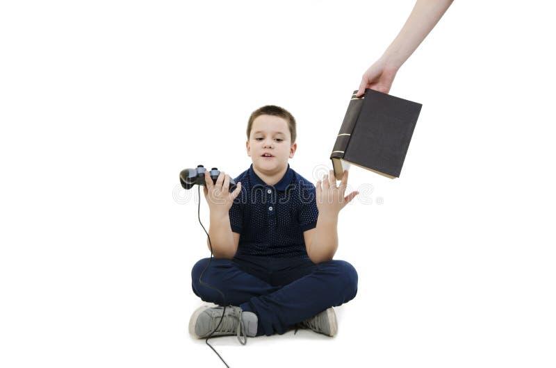 Förargad pojke Handen för ` s för modern för pyslekvideospel sätter honom en bok för att lära arkivfoton