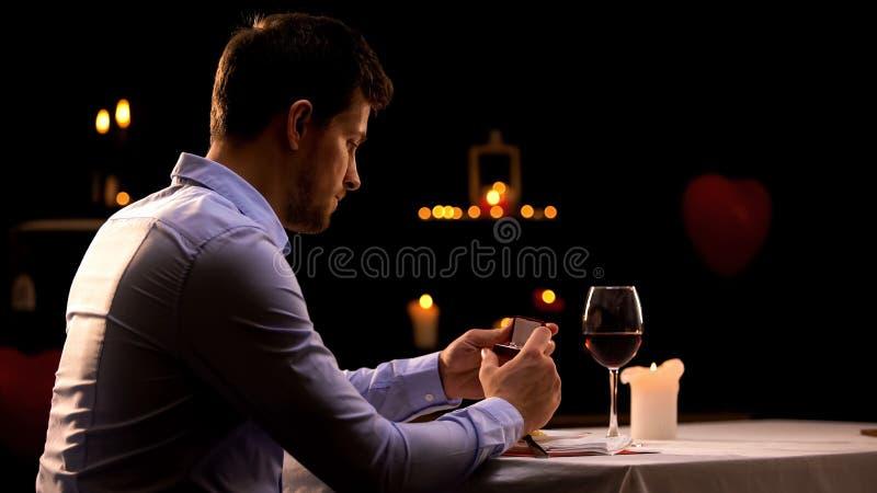 Förargad stilig man som ser asken med den dyrbara cirkeln i restaurang, ensamhet royaltyfri foto