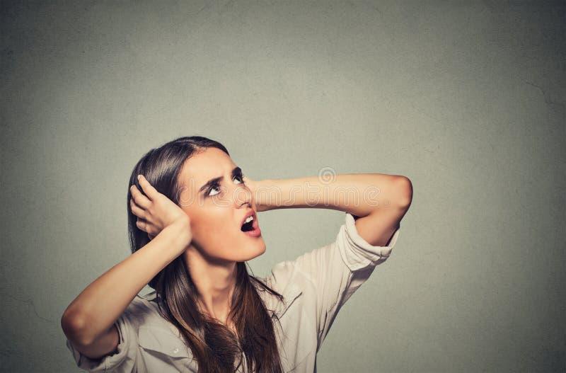 Förargad stressad kvinna som täcker henne öron som upp uppför trappan ser högt oväsen royaltyfri fotografi