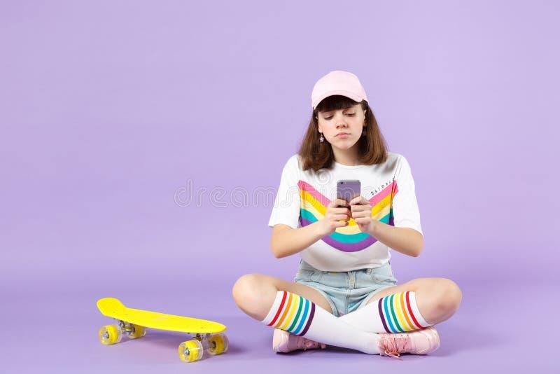 F?rargad ton?rig flicka i livlig kl?der som sitter n?ra skateboarden, genom att anv?nda mobiltelefonen som skriver det isolerade  arkivfoton