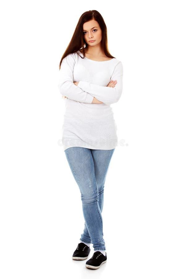 Förargad ung kvinna med korsade armar fotografering för bildbyråer