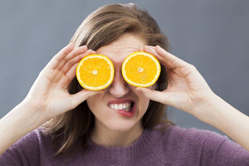Förargade hållande apelsinskivor för ung kvinna på ögon som exponeringsglas arkivfoton