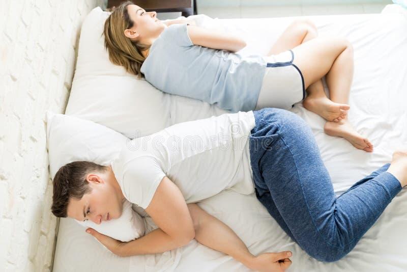 Förargade multietniska par som hemma ligger på säng fotografering för bildbyråer