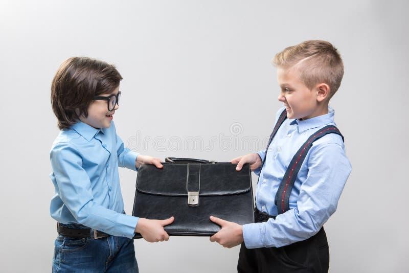 Förargade ungar som spelar leken av affärskonkurrenter royaltyfri fotografi