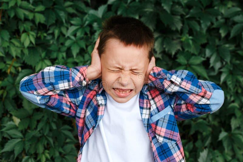 Förargat belastade pojken, räkningsöron känner att den gjorde ont öraknipet smärtar arkivbild