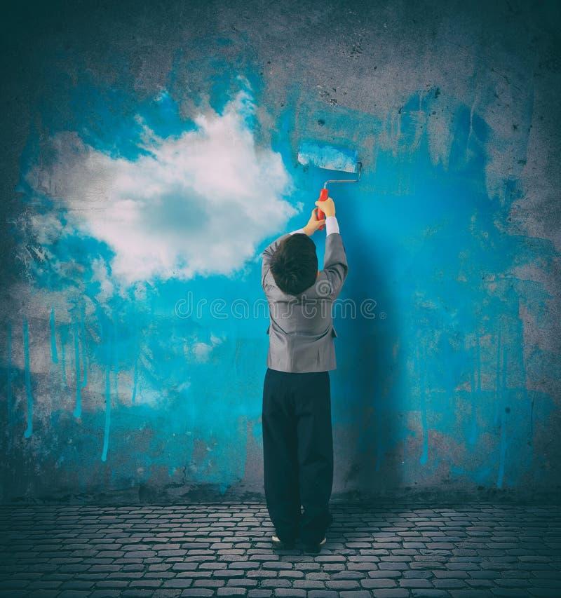 Förbättra ditt perspektiv Barnet målar en himmel på en grå vägg royaltyfri foto