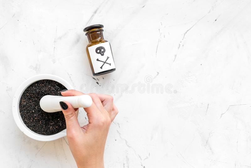 Förbered gift Flaska med skallen och korslagda benknotor nära handen som gör pulver i mortel på den vita kopian för den bästa sik fotografering för bildbyråer