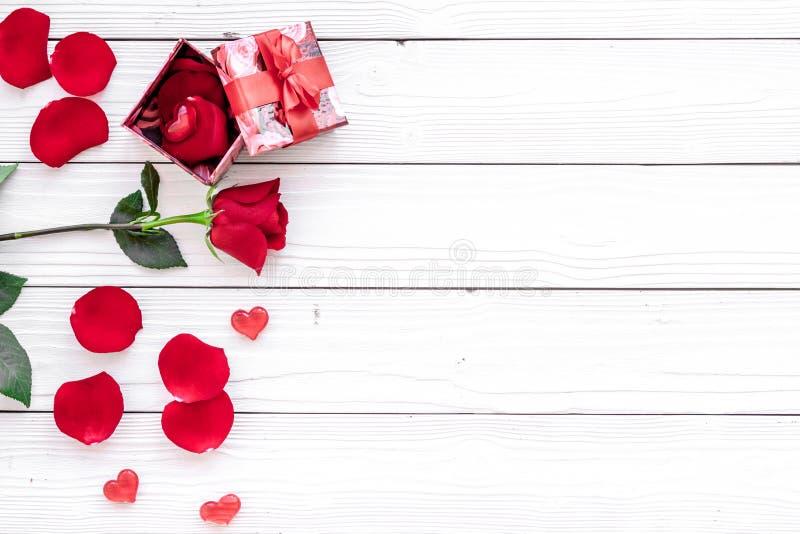 Förbered prsesntsna eller förvåna för dag för valentin` s Röd gåvaask nära röd ros och kronblad på vit träbakgrund royaltyfri fotografi