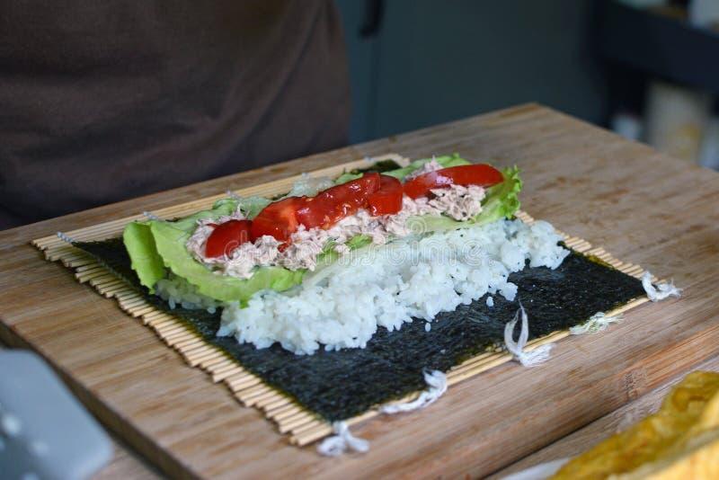 Förbereda den hemlagade sushi med vita ris, tonfisk, tomater och sallad på ett torkat norihavsväxtark på matt bambu royaltyfri foto