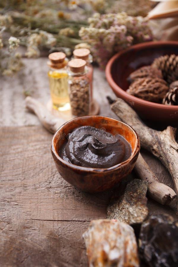 Förbereda den kosmetiska svarta gyttjamaskeringen i keramisk bunke på tappningträbakgrund Främre sikt av ansikts- leraemulsion på royaltyfria foton