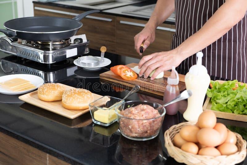 Förbereda den läckra hamburgaren i kök hemma royaltyfri fotografi
