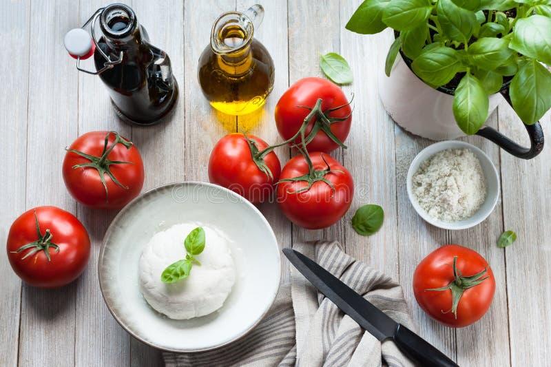 Förbereda en Caprese för strikt vegetariansommartomat sallad arkivbilder