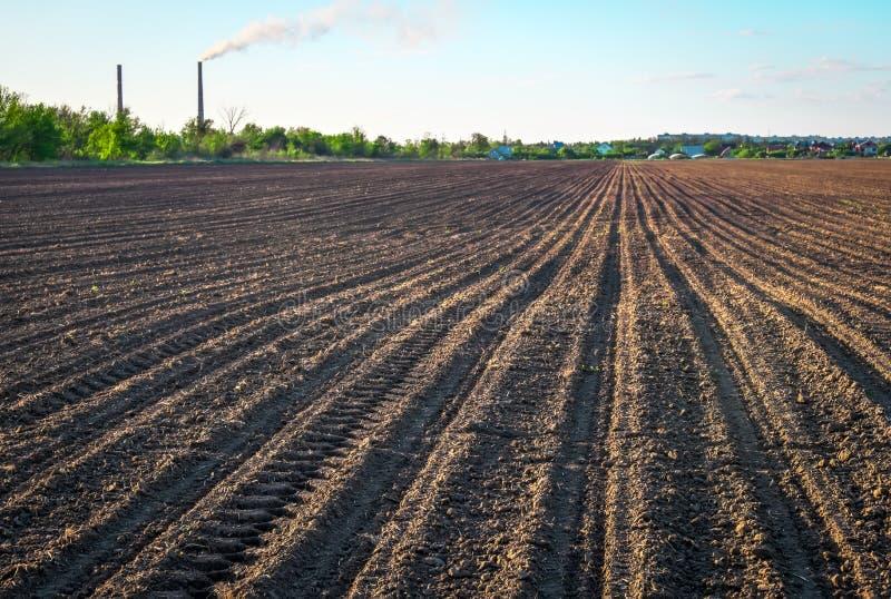 Förbereda fältet för att plantera Plogad jord i vårtid, två rör arkivfoto