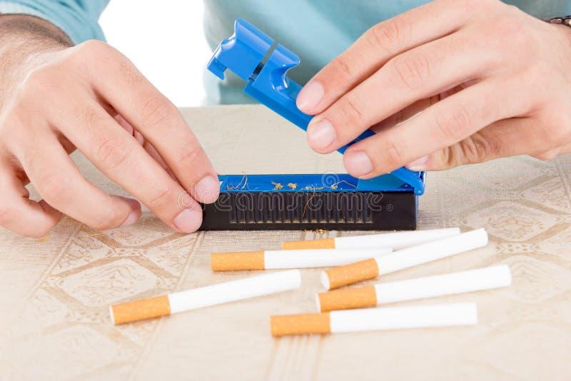 Förbereda handgjorda cigaretter genom att använda rullningar och tobak royaltyfria foton