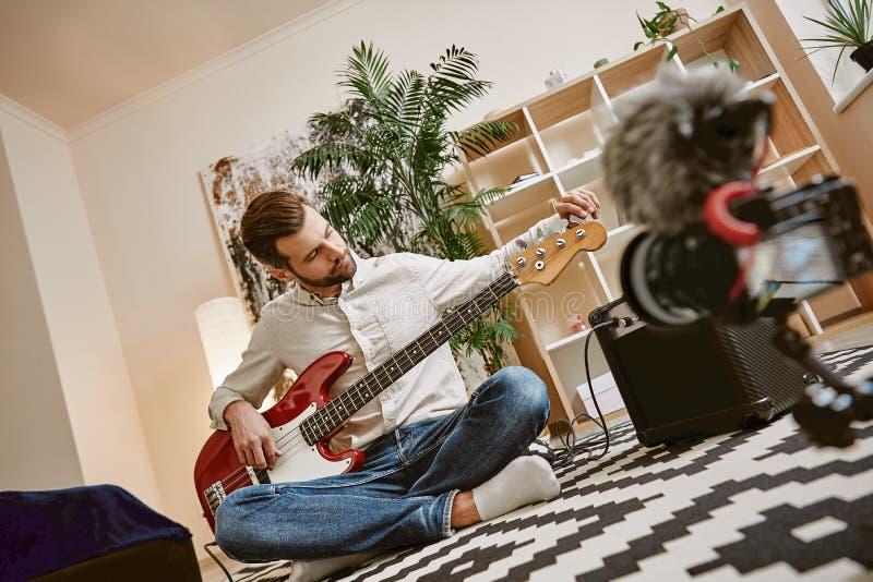 Förbereda instrumentet Stilig manlig musikblogger som justerar den elektriska gitarren för att anteckna ny video kurs royaltyfria foton
