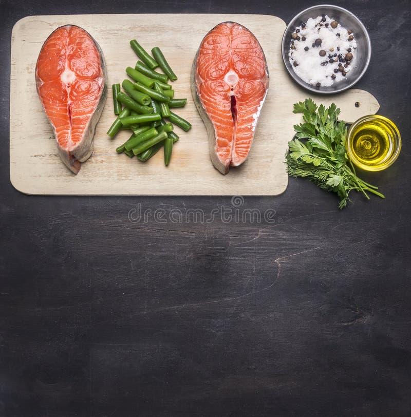 Förbereda rå laxbiff med örter, salt, peppar och andra smaktillsatser, ligger två biffar på skärbrädan, på svart backgr royaltyfri fotografi