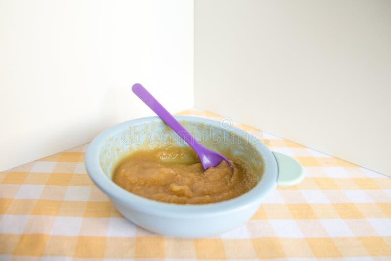 Förbereda sig behandla som ett barn mat som är hemlagad Bästa sikt av en bunke med blandade kokta äpplen i en blå bunke på en bor royaltyfria bilder