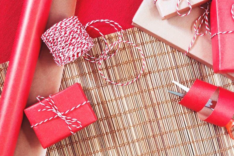Förbereda sig för ferien - gåvainpackning i rött och beige inpackningspapper royaltyfria bilder