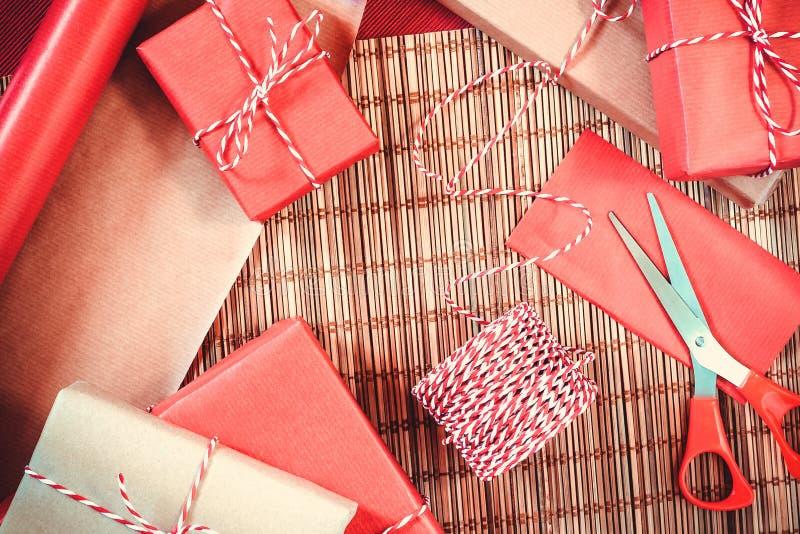 Förbereda sig för ferien - gåvainpackning i rött och beige inpackningspapper royaltyfri fotografi