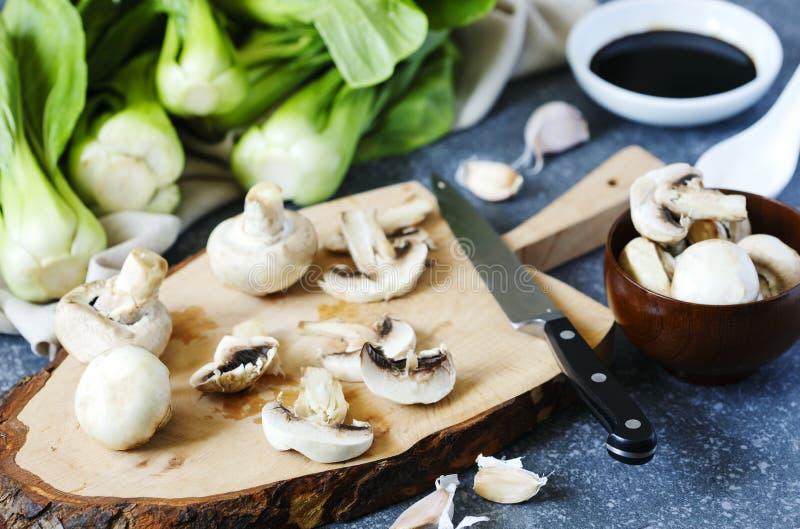 Förbereda sig för kinesiskt mål Matlagningingredienser: choy bok, champinjoner, vitlök och soya royaltyfria bilder